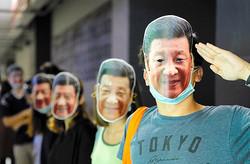 香港で18日にあった覆面禁止法に抗議するデモで、中国の習近平国家主席のお面を着用した参加者=AP