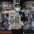 インドネシア・スラバヤの港で、オーストラリアから違法に輸入されたごみが詰まったコンテナに入っていた新聞を見せる税関職員(2019年7月9日撮影)。(c)Juni Kriswanto / AFP