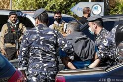 レバノンの首都ベイルート近郊のバーブダで、脱走した収容者を捕らえて連行する警官ら(2020年11月21日撮影)。(c)ANWAR AMRO / AFP