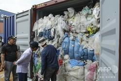 インドネシア・バタム島の港で、プラスチックごみが詰まったコンテナを調査する地元税関職員ら(2019年6月15日撮影)。(c)ANDARU / AFP