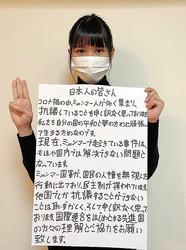 ミャンマーの危機を訴えるメッセージを日本語で書いたウィンさん。3本指のサインは独裁への反対を表している=本人提供