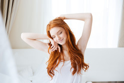 Sensual smiling redhead young woman with long hair sitting and stretching in bed