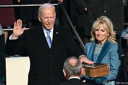 米連邦議会議事堂で行われた大統領就任式で、就任宣誓するジョー・バイデン新大統領。隣は妻のジル・バイデン氏(2021年1月20日撮影)。(c)SAUL LOEB / POOL / AFP