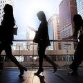 香港中央地区の高架歩道を歩くビジネスウーマンのシルエット