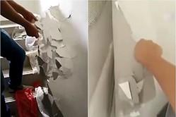 北京市民の顧さんは購入した物件を検収した際、壁が簡単に剥がせ、壁の中にびっしりとビニール袋が詰め込まれているのを見つけた(スクリーンショット)