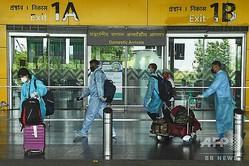 インドのコルカタにある空港で、マスクと保護服を身に着けた乗客(2020年7月6日撮影、資料写真)。(c)Dibyangshu SARKAR / AFP