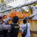 インドネシア・リアウ州バタム島にある海軍の軍港で、中国漁船からインドネシア人船員の遺体を降ろす当局者ら(2020年7月8日撮影)。(c)TEGUH PRIHATNA / AFP