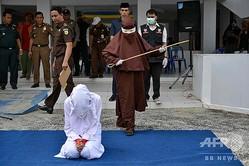 インドネシアのアチェ州の州都バンダアチェで、公開むち打ちの刑の執行を待つ女性(2019年12月10日撮影)。(c)Chaideer MAHYUDDIN / AFP