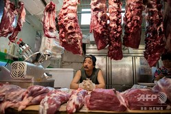 中国・北京の市場で客を待つ肉の販売業者(2019年7月10日撮影)。(c)NICOLAS ASFOURI/AFP
