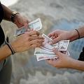 キューバの首都ハバナの両替所前で同国の通貨ペソの紙幣を点検する人たち(2020年12月15日撮影、資料写真)。ADALBERTO ROQUE / AFP