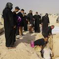 イラク・聖地ナジャフ郊外の砂漠に設置された「新型コロナウイルス墓地」で、改葬のために親族の遺体を掘り返すイラク人家族(2020年9月11日撮影)。(c)AFP