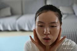 視覚障害者向けのオンラインメーキャップ教室を自宅で開く元マッサージ療法士の視覚障害者シャオ・ジアさん。中国・北京で(2020年7月13日撮影)。(c)GREG BAKER / AFP