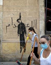 レバノン・ベイルートの爆発被害を受けた地域で、首をつるされた政治家の絵と、アラビア語で「死刑」と書かれた壁画の前を歩く市民活動家ら(2020年8月7日撮影)。(c)PATRICK BAZ / AFP