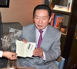 ファンのために、自伝本にサインをする生前の野粼幸助氏。特徴ある筆跡で自身の名前を書いた