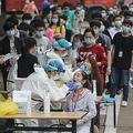 数百万人規模で行われるPCR検査では、ボランティアが作業を手伝う(写真/AFP=時事)