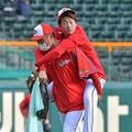 練習を途中で切り上げ、永川コーチに背負われてグラウンドを後にする大瀬良