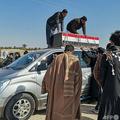 イラク南部のナシリヤで、奇襲攻撃の犠牲者のひつぎをのせた車両に集まり、哀悼の意を表す人々(2021年1月24日撮影)。(c)Asaad NIAZI / AFP