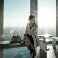 モダンな高層ビルのベンチに座る女性