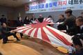 「戦犯放射能2020東京五輪阻止ネットワーク」の発足式で、出席者たちが旭日旗を破っている