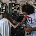 パキスタン東部ラホールの理髪店で、肉切り包丁とガスバーナーを使って髪を切るアリ・アッバスさん(2021年4月8日撮影)。(c)Arif ALI / AFP