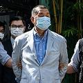 香港で、国家安全維持法(国安法)に違反した疑いで逮捕され、自宅から連行される黎智英(ジミー・ライ)氏(中央、2020年8月10日撮影)。(c)VERNON YUEN / AFP