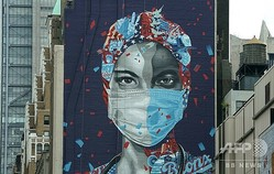 米ニューヨーク・マンハッタンで、建物の壁に描かれた医療従事者の顔(2020年5月11日撮影、資料写真)。(c)TIMOTHY A. CLARY / AFP