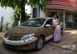 牛ふんと泥を混ぜ合わせたものを塗りつけた車の横に立つセジャルベン・シャーさん。インド・アーメダバードにて(2019年5月23日撮影)。(c)SAM PANTHAKY / AFP