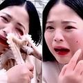 タコの吸盤を必死に剥がそうとする女性(画像は『Business Insider Singapore 2019年5月8日付「An octopus sucked onto a vlogger's face and ripped her skin when she tried to eat it live on camera」(Seaside Girl Little Seven / Kuaishou)』のスクリーンショット)
