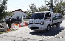 金浦の養豚場周辺で消毒作業を行う車両=23日、金浦(聯合ニュース)