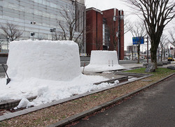 かまくらづくりのため市外から運び込まれ、積まれた雪。周囲にはまったく雪がない=秋田県横手市の市庁舎前で2020年1月14日午後3時22分、佐藤伸撮影