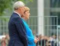 独首都ベルリンで、同国を訪問中のフィンランドのアンティ・リンネ首相(左)とともに、国歌の演奏を聴くアンゲラ・メルケル首相(2019年7月10日撮影)。(c)AFP=時事/AFPBB News