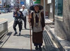 すげがさに杖をつき歩く吉田執行長。動画配信のカメラが同行している(大阪府摂津市)
