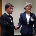 握手する康氏(右)と茂木氏=26日、ニューヨーク(聯合ニュース)