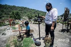メキシコのサンミゲルヒコ墓地で、新型コロナウイルスにより亡くなった家族2人の墓を訪れた女性と、墓に十字架をたてる少年(2020年8月5日撮影)。(c)PEDRO PARDO / AFP