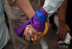 虹色の旗を巻き付けた手をつなぐカップル(2018年6月30日撮影、資料写真)。(c)TED ALJIBE / AFP