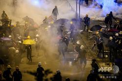 香港の政府庁舎付近でデモ隊に催涙ガスを浴びせる警察(2019年7月2日撮影、資料写真)。(c)Anthony WALLACE / AFP