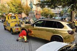 ドイツ・デュッセルドルフで、路上から撤去される金色のBMW「X5」(2019年10月13日撮影)。(c)Gerhard BERGER / DPA / AFP