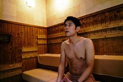 サウナのベンチ下段に座り汗をかく原田泰造