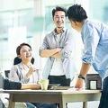 若手の管理職社員のグループがオフィスでコミュニケーションをとっている