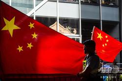 中国旗の前に立つ警察官(2018年7月1日撮影、資料写真)。(c)Philip FONG / AFP