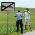 オーストリアのフッキング村で、標識の前で記念撮影する旅行者(2008年6月18日撮影)。(c)Mladen ANTONOV / AFP
