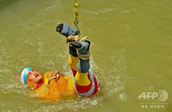 インド・コルカタにあるフーグリー川にクレーンによってつり下ろされるマジシャンのチャンチャル・ラヒリさん(2019年6月16日撮影)。(c)STR / AFP