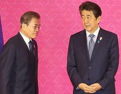 韓国の文在寅大統領(左)を見つめる安倍首相(ロイター)
