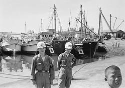 韓国当局に拿捕されて釜山港に連行された日本漁船と、その警備にあたる憲兵(1955年12月/写真=時事通信フォト)
