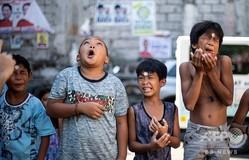 カッシアの聖リタの祭りで、コインを額から口に移動させるゲームに挑戦する子どもたち。フィリピン・マニラにて(2019年5月19日撮影)。(c)Noel CELIS / AFP