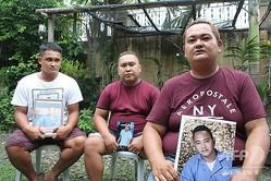 フィリピン中部イロイロ州ディングルで豪華クルーズ船の技師チェロキー・カパジョさんの写真を持つ兄弟(2020年6月29日撮影)。(c)AFP