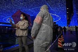 中国・湖北省武漢のショッピングモール入り口で自らの健康情報をスマートフォンで確認する買い物客(2020年4月18日撮影)。(c)Hector RETAMAL / AFP