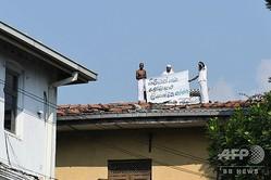 スリランカの中心都市コロンボにあるウェリカダ刑務所で、屋根の上から横断幕を広げる受刑者ら(2019年11月12日撮影)。(c)Lakruwan WANNIARACHCHI / AFP
