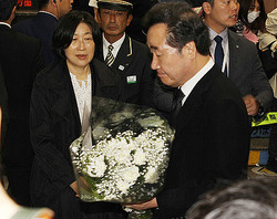 JR新大久保駅で、2001年の事故で死亡した李秀賢さんらを追悼するため献花する韓国の李洛淵首相(右)=22日、東京都新宿区