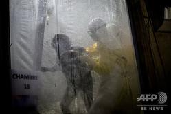 コンゴ民主共和国キブ州ブテンボで、国境なき医師団(MSF)の支援を受けて運営されているエボラ治療センター(ETC)で、感染が疑われる患者を看病する医療従事者(2018年11月3日撮影、資料写真)。(c)AFP / John Wessels